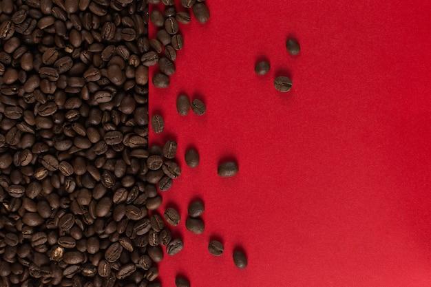Os grãos de café são espalhados em um close de papel vermelho, copyspace comercial.