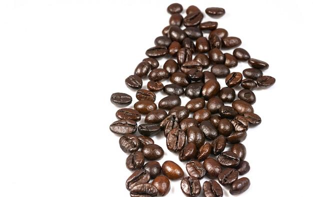 Os grãos de café torrados chapinham isolado em um fundo branco.