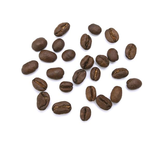 Os grãos de café torrados empilham de cima no branco