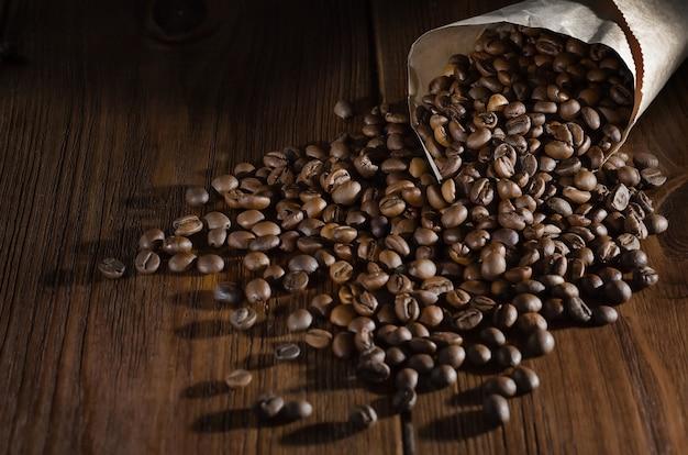 Os grãos de café torrados encontram-se em um saco de papel e estão espalhados sobre um fundo de madeira. vista de cima