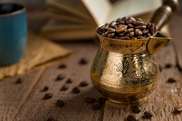 Os grãos de café torrados frescos no cezve abriram o livro e o copo na mesa de madeira.