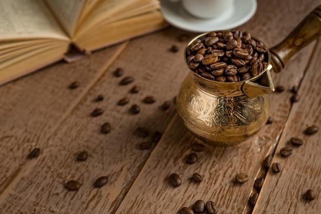 Os grãos de café torrados frescos no cezve (bule de café turco tradicional) abriram o livro e o copo na mesa de madeira.