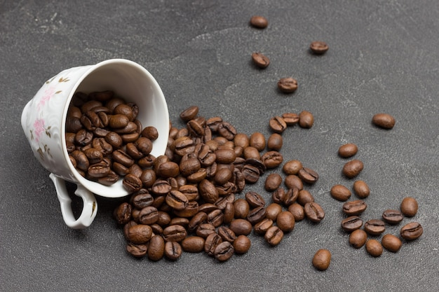Os grãos de café torrados são espalhados da xícara sobre a mesa. fundo preto. vista do topo