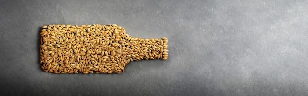 Os grãos de malte são dispostos como uma garrafa de cerveja em um fundo cinza de concreto.