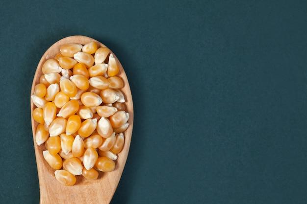 Os grãos de milho seco em uma colher de pau são colocados em uma placa verde copyspace