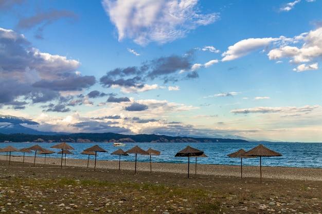 Os guarda-chuvas de praia da palha na costa vazia do mar negro na abkhásia, pitsunda no por do sol. praia de calhau, montanhas, mar, céu com nuvens