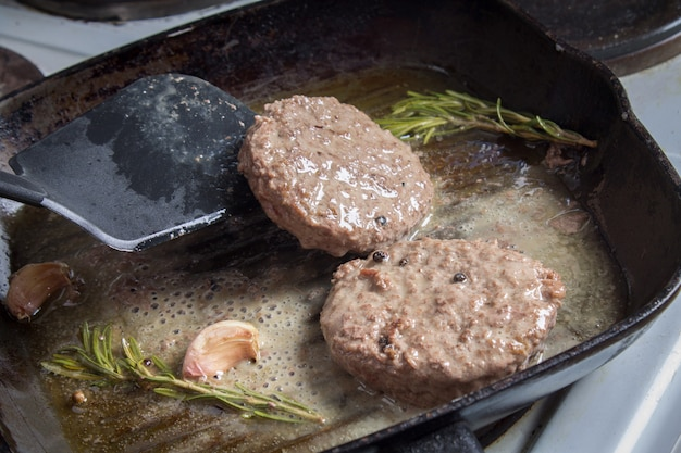 Os hambúrgueres são fritos em uma panela com alecrim e alho.