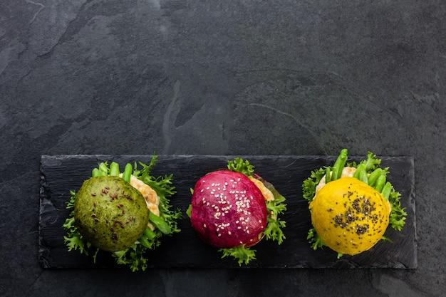 Os hamburgueres verdes, amarelos e roxos coloridos na ardósia embarcam. vista do topo