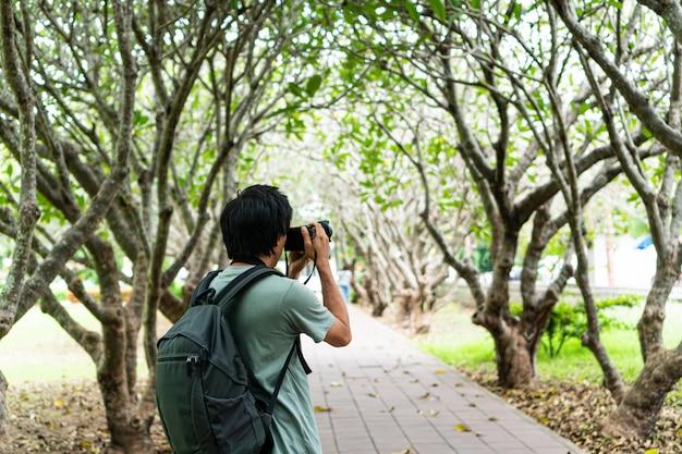 Os homens asiáticos dão um passeio e tiram uma foto no parque.