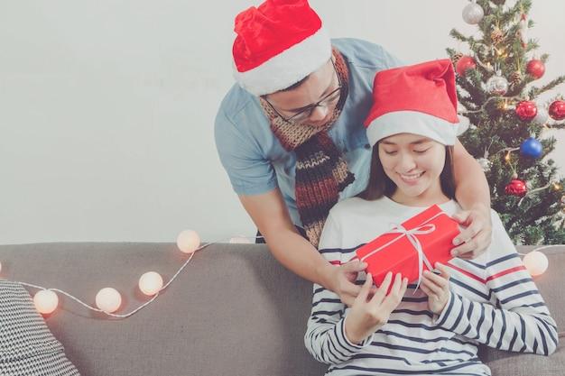 Os homens asiáticos dão uma caixa de presente a belas mulheres asiáticas jovens. rindo rosto no quarto com a decoração da árvore de natal para o fundo do feriado. sobre o casal e o conceito de celebração.