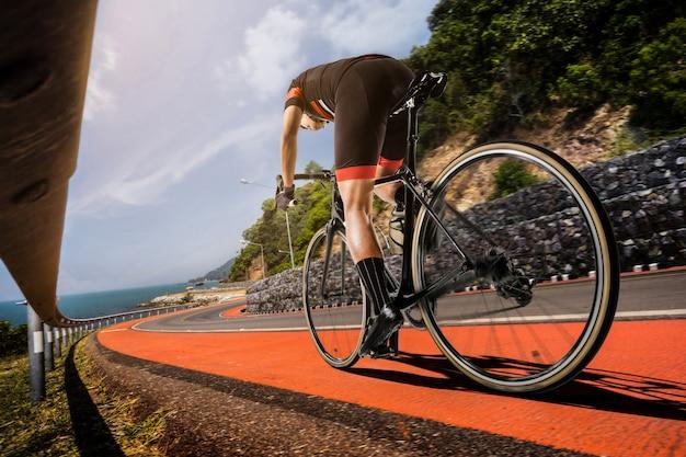 Os homens asiáticos estão andando de bicicleta de estrada pela manhã