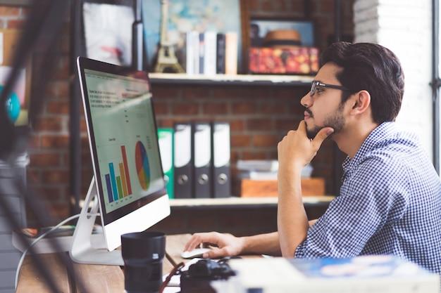 Os homens asiáticos estão assistindo a um gráfico de um computador no escritório.