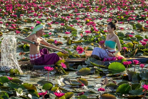 Os homens asiáticos estão coletando flores de lótus vermelhas para mulheres asiáticas para adorar. a cultura do povo tailandês.