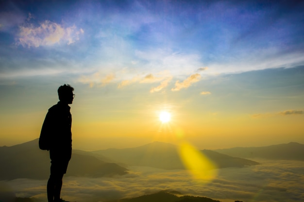 Os homens asiáticos estão olhando a névoa e o nascer do sol.
