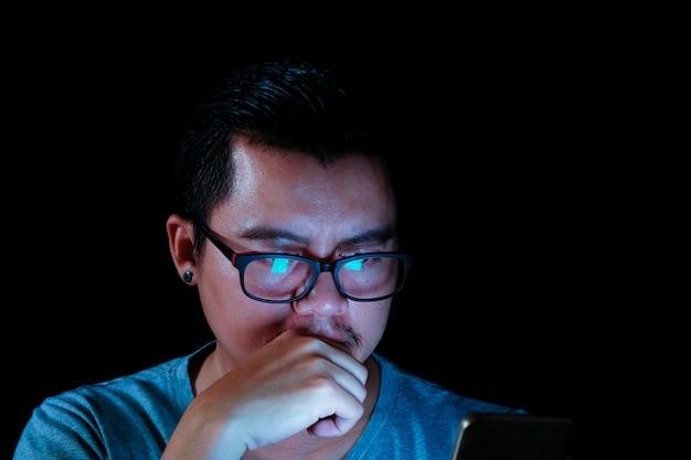 Os homens asiáticos estão usando o telefone ou a tabuleta com uma luz azul na escuridão, efeitos do conceito da tecnologia.