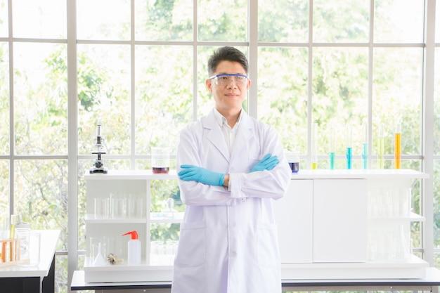Os homens asiáticos tailandeses usam óculos de proteção e luvas resistentes a produtos químicos. no laboratório, há um pano de fundo em um tubo de ensaio contendo uma grande quantidade de substâncias pela manhã.