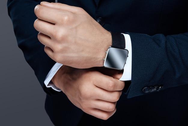 Os homens assistem na mão com close-up do relógio.