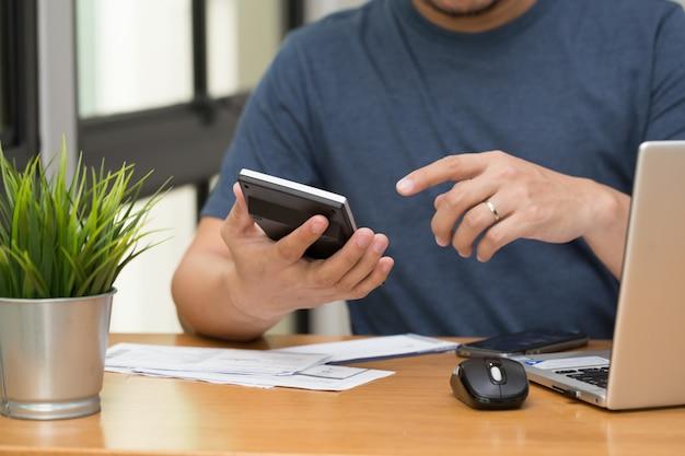 Os homens calculam o saldo do pagamento da dívida do cartão de crédito e do empréstimo mensal