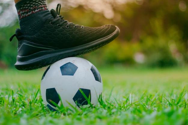 Os homens colocam os pés na bola de futebol.