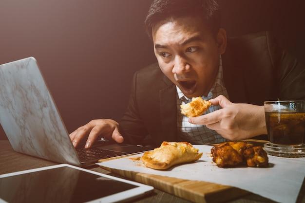 Os homens de negócios estão comendo a pizza e os pés de galinha do bbq na mesa.