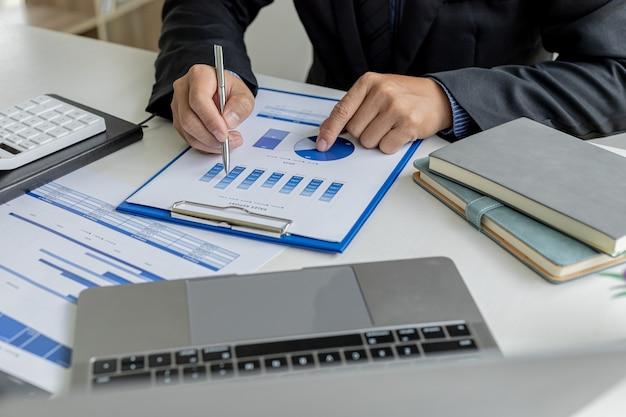 Os homens de negócios examinam os documentos financeiros da empresa para analisar problemas e encontrar soluções antes de levar as informações para uma reunião com um parceiro. conceito financeiro.