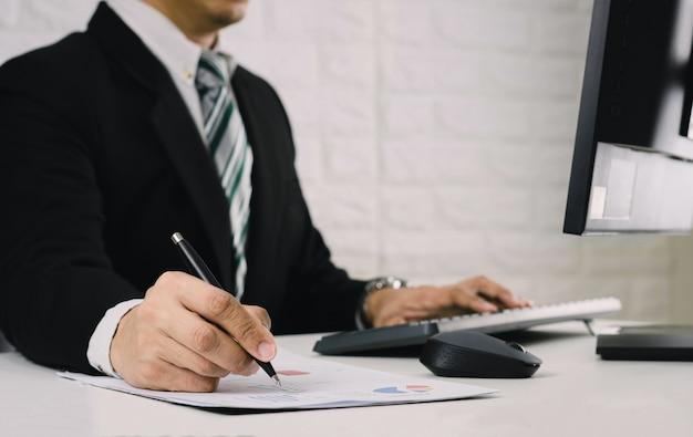 Os homens de negócios trabalham em cima da mesa analisar o relatório financeiro de gráficos em documentos e computadores.