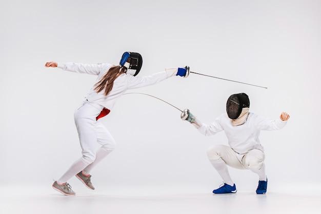 Os homens e a mulher vestindo terno de esgrima praticando com espada contra cinza