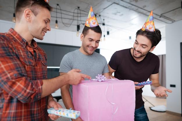 Os homens em chapéus de aniversário estão mostrando uns aos outros presentes.