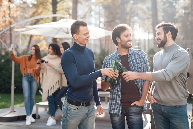 Os homens em primeiro plano estão sorrindo e bebendo cerveja.