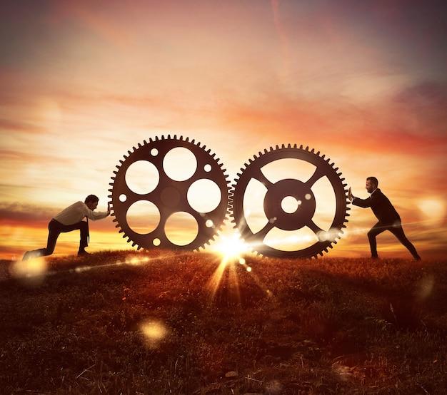 Os homens empurram duas engrenagens ao pôr do sol na montanha. conceito de cooperação no trabalho