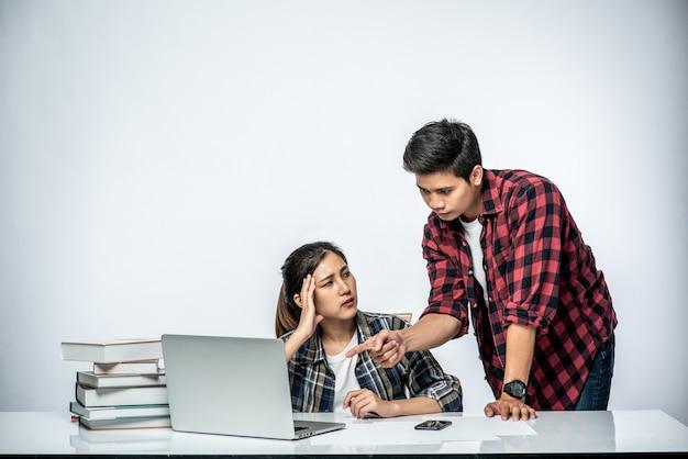 Os homens ensinam as mulheres a trabalhar com laptops no trabalho.
