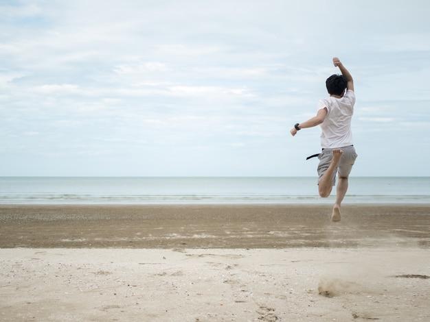 Os homens estão de bom humor. feliz pulando pronto para lutar na praia.