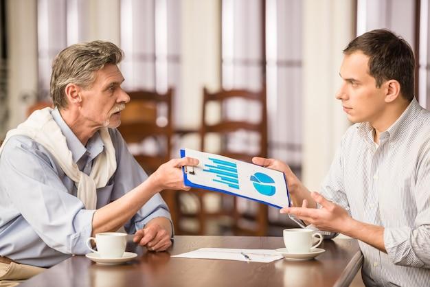 Os homens estão discutindo projetos importantes e olhando para o gráfico.