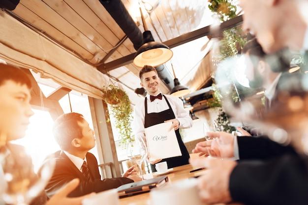 Os homens estão escolhendo vinho no restaurante