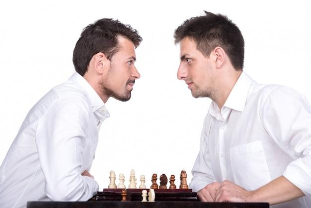 Os homens estão jogando xadrez e olhando um para o outro.