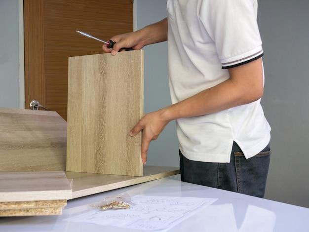 Os homens estão montando, diy seus próprios móveis de madeira.