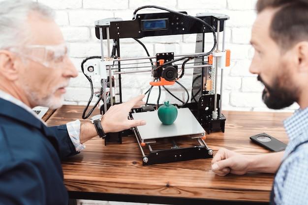 Os homens estão olhando para o resultado do trabalho da impressora 3d.
