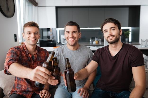 Os homens estão sentados no sofá e bebem cerveja de garrafas