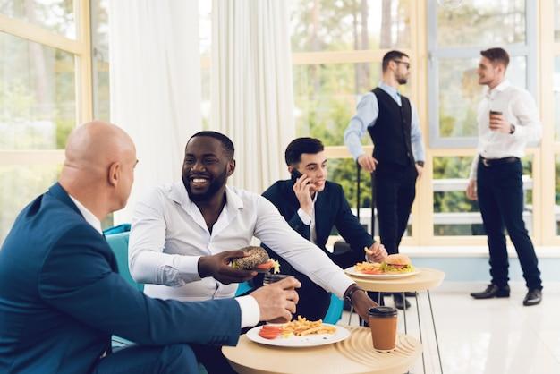 Os homens estão vestidos em trajes na sala de espera.