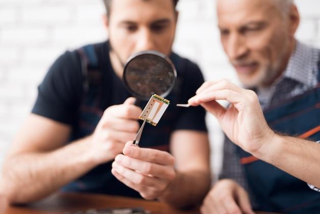 Os homens examinam o componente do pc com lupa.