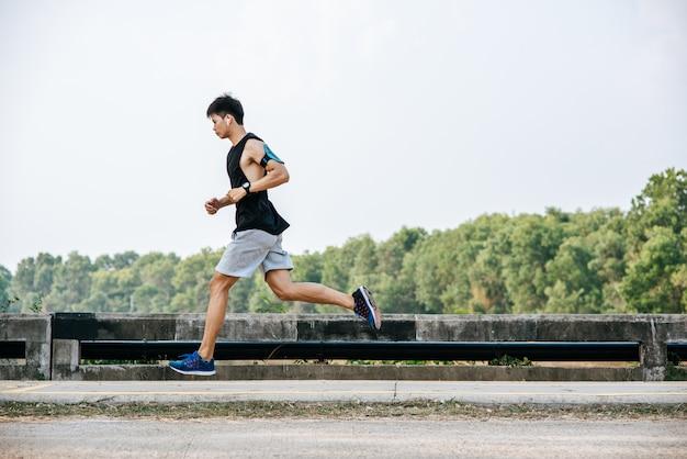 Os homens exercitam correndo na estrada na ponte.