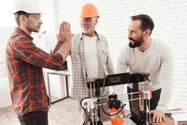 Os homens ficam três juntos em torno da impressora 3d.