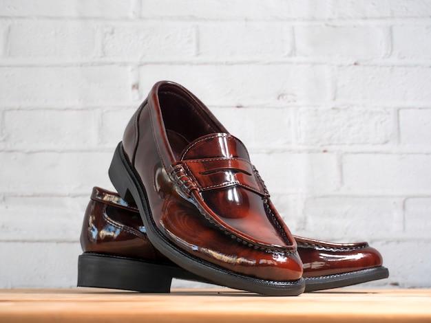 Os homens formam sapatos preguiçosos de borla na madeira.