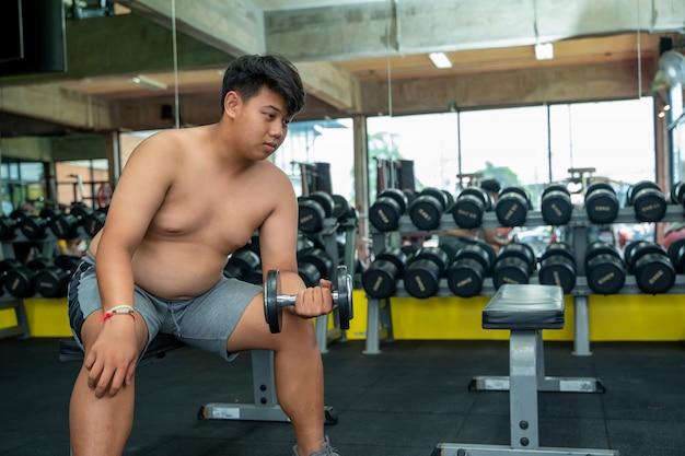 Os homens gordos exercitam no ginásio, jovem, segurando um haltere no clube de fitness.