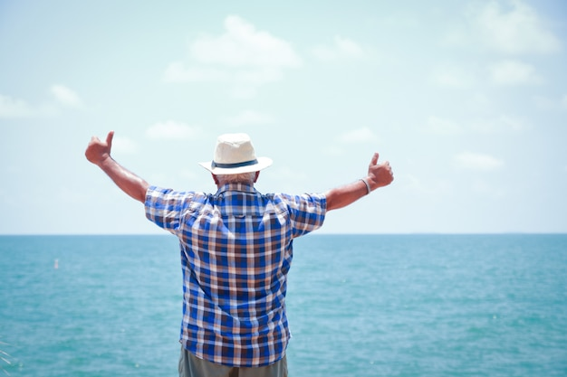 Os homens idosos vêm visitar o mar. de pé, voltando-se, espalhar os dois braços, fazendo as mãos, polegares para cima, agradando