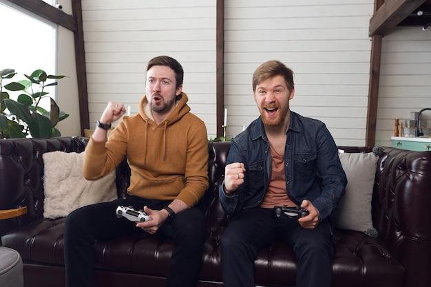 Os homens jogam videogame e se alegram emocionalmente com a vitória, um momento divertido em casa. foto de alta qualidade