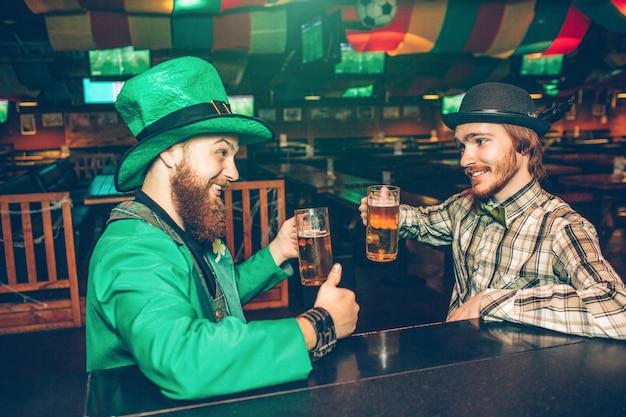 Os homens novos felizes alegres sentam-se na frente no balcão da barra no bar. eles comemoram e seguram canecas de cerveja. o cara da esquerda veste o traje verde do st. patrick.