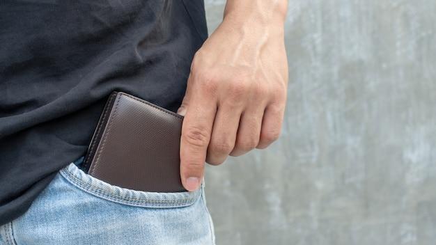 Os homens seguram uma carteira marrom no bolso da calça jeans.