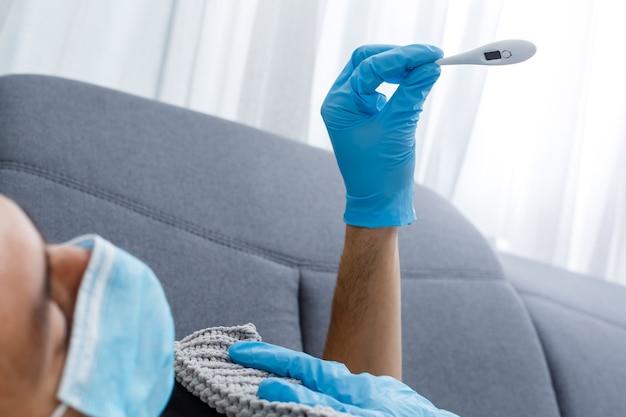 Os homens sentem frio e enjoos por causa do vírus corona. ele usa um termômetro para verificar a temperatura corporal