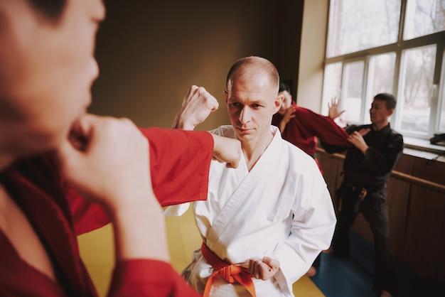 Os homens trabalham fora a técnica karate de impacto no ginásio